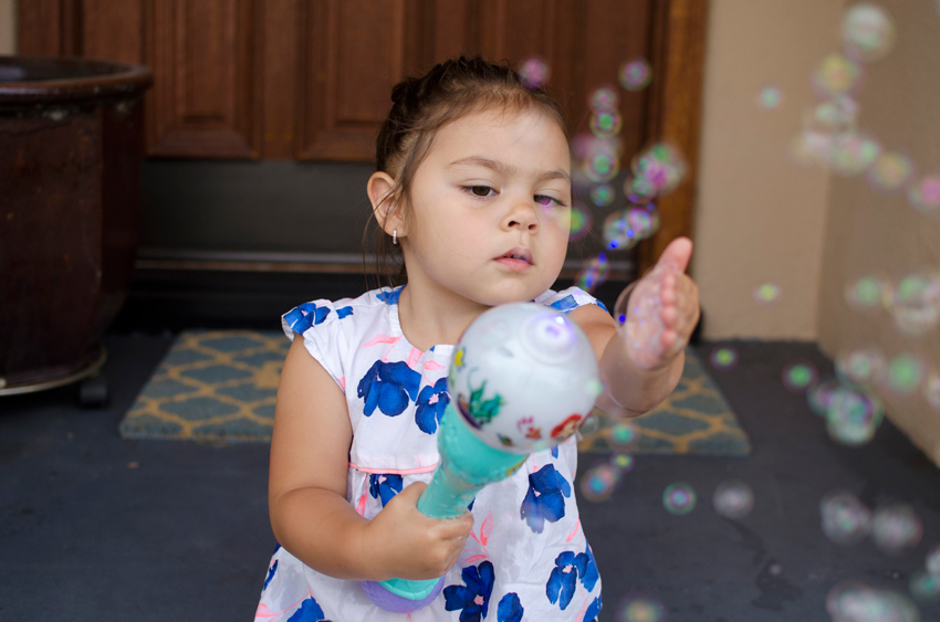 portrait of toddler playing with bubbles